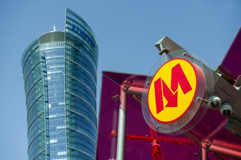 zdjęcie logo Metra Warszawskiego na tle budynku