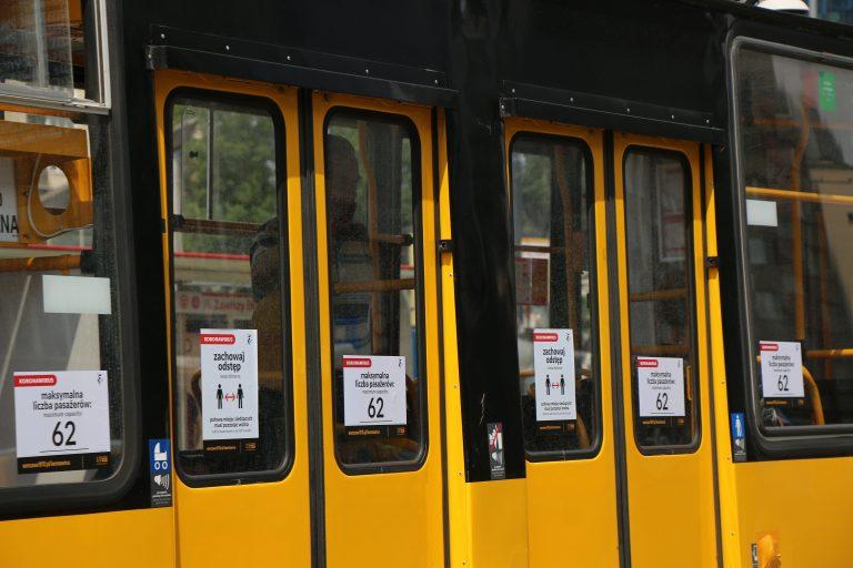 zdjęcie pokazujące naklejki na drzwiach tramwaju z limitem osób