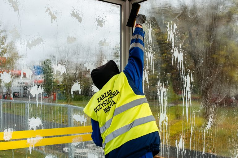 zdjęcie - Pracownik służb oczyszczania miasta myje szybę w wiacie przystankowej