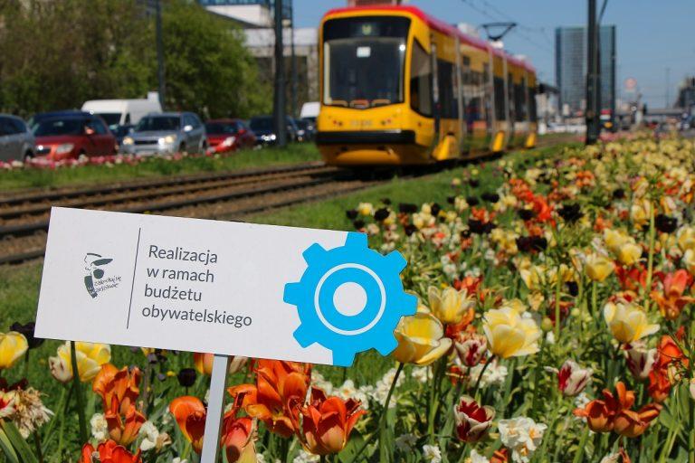 Kwiaty i tramwaj w tle. Tabliczka o budżecie obywatelskim