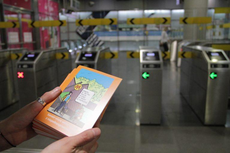 """Zdjęie okładki poradnika """"Savoir-vivre wobec osób z niepełnosprawnością"""" na tle bramek wejściowych na stację metra"""