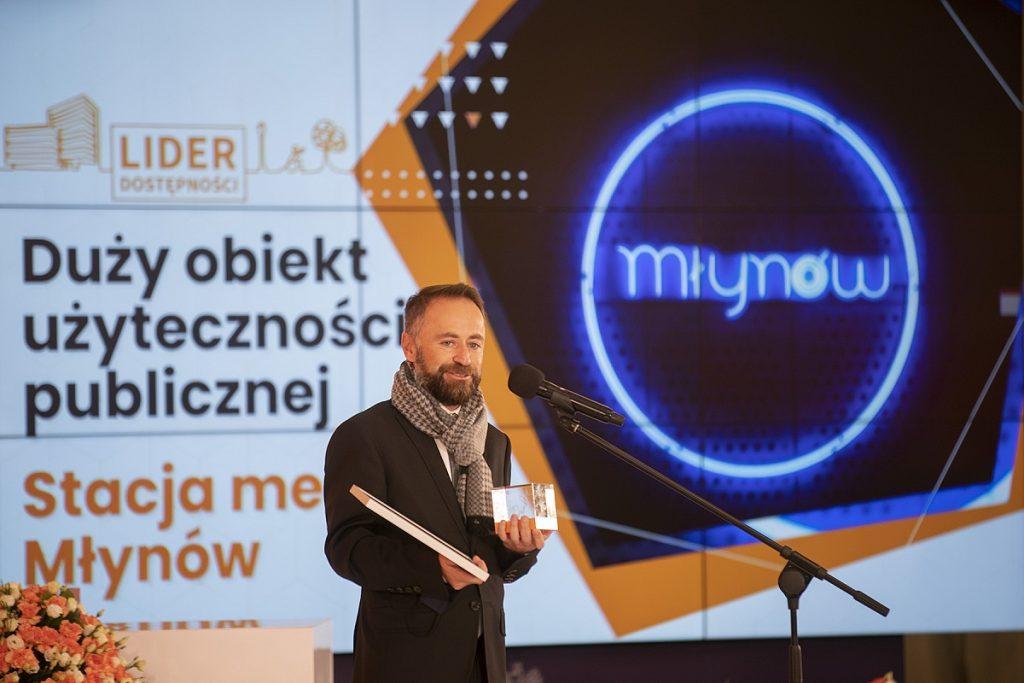 Zdjęcie wiceprezydenta m.st. Warszawy Michała Olszewskiego odbierającego nagrodę Lidera Dostępności 2021 dla stacji metra Młynów